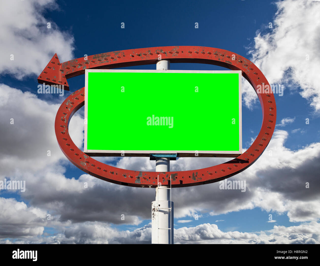 Vintage arrow sign with chroma key green insert and clouds. - Stock Image