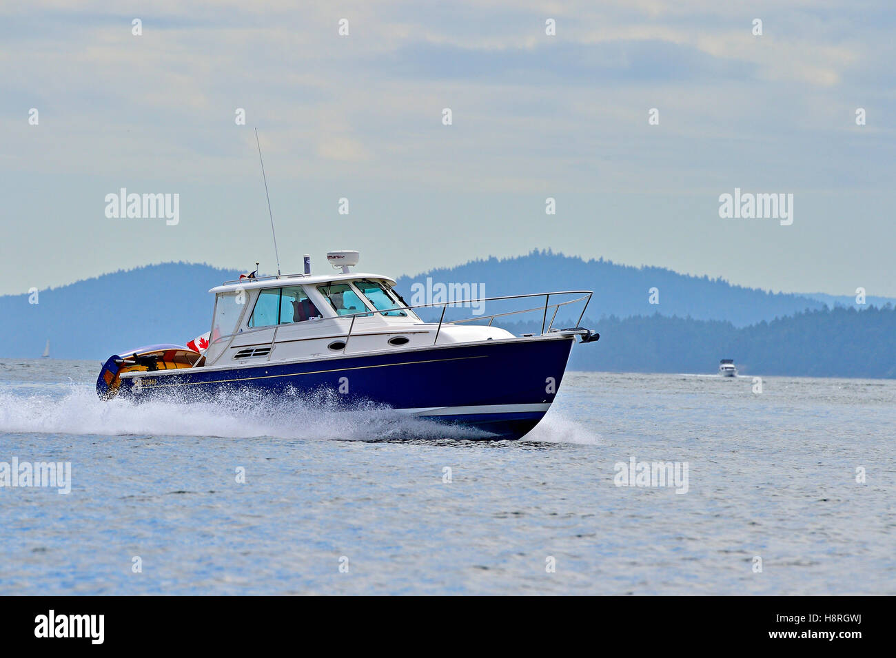 A motor boat cruising along at the calm waters of the Strait of Georgia  near Vancouver Island British Columbia Canada