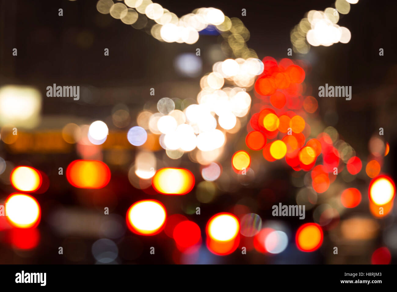 Blurred car lights. Out of focus traffic lights of cars on the sreet. Bokeh lights from traffic jam on night time - Stock Image
