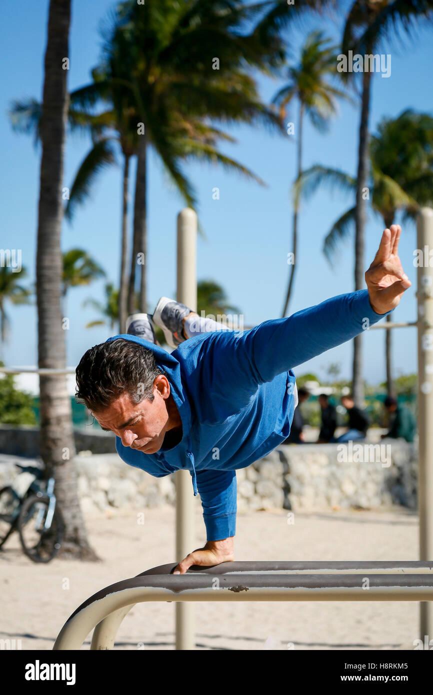 Miami Beach, Florida.  Man balances on work out beam at South Beach - Stock Image