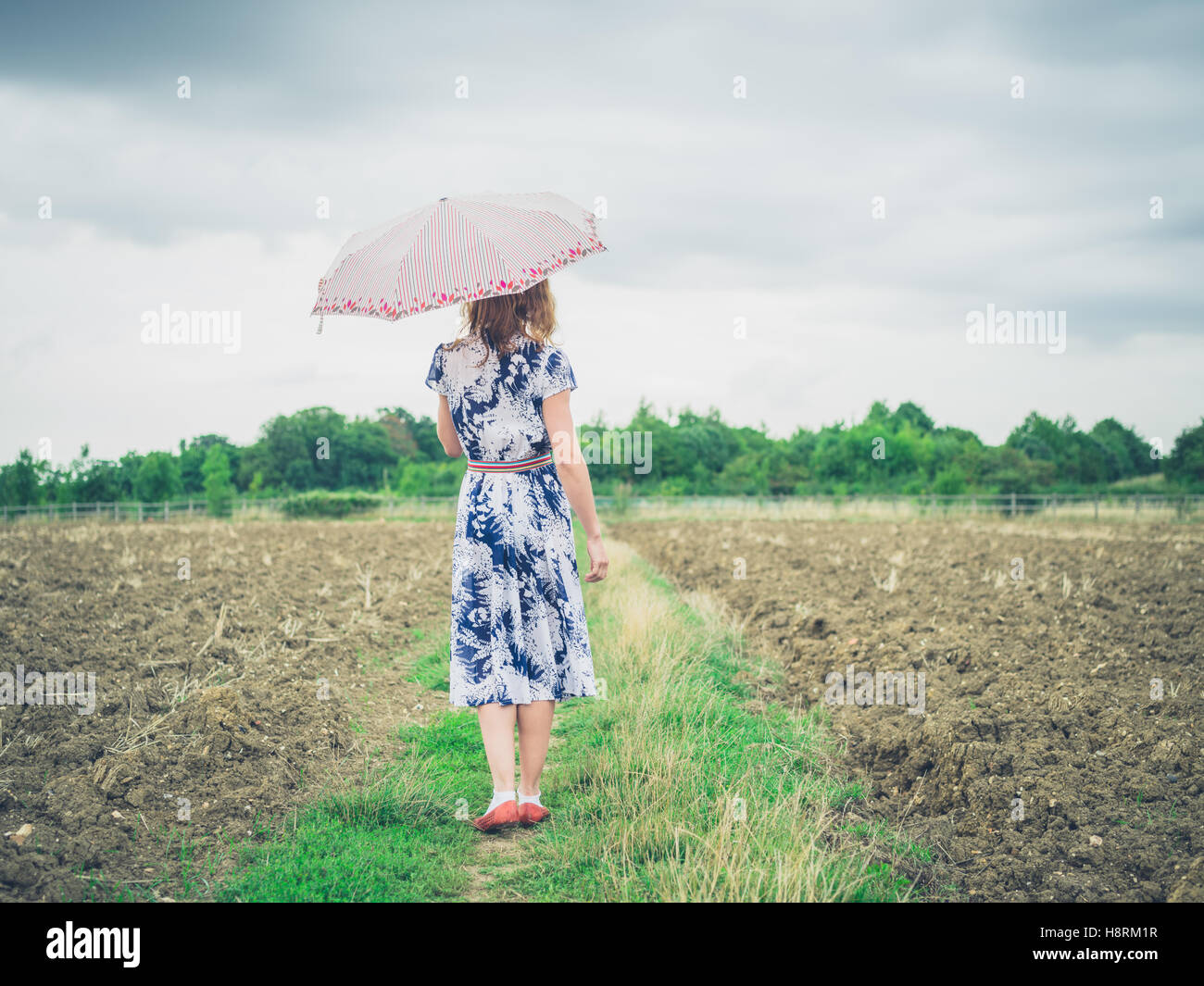 A young woman wearing a dress is walking in a barren field with an umbrella - Stock Image