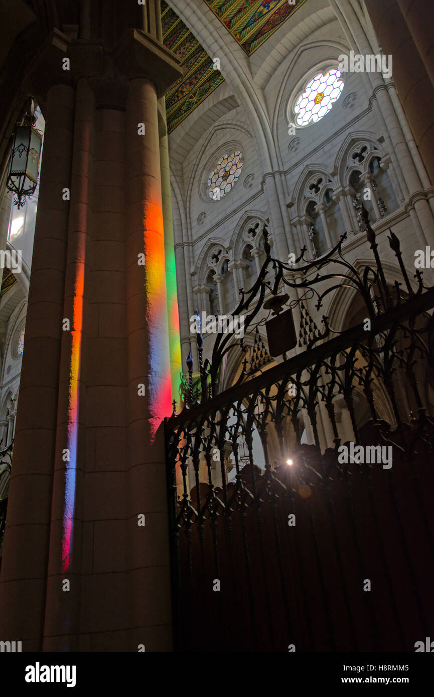 Rainbow colors projected on a column from stained glass windows in the 'Almudena'  Madrid cathedral - Stock Image