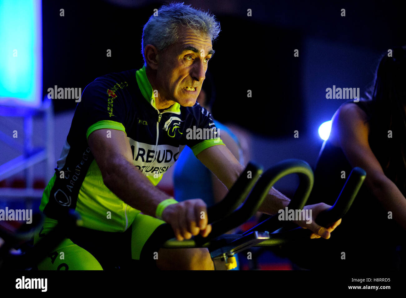 Man riding stationary bicycle during a spinning class at the gym - Stock Image