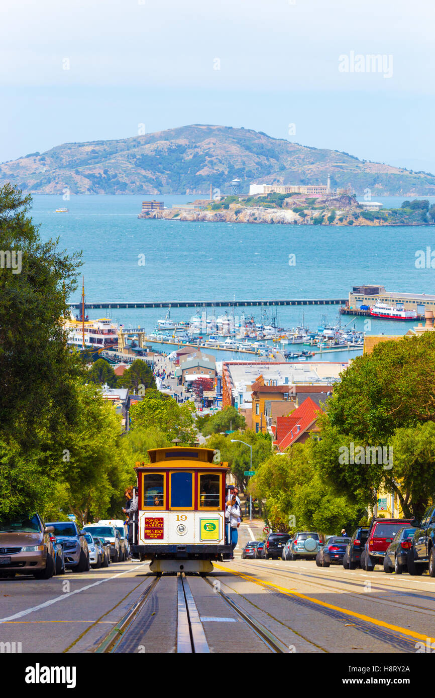 Approaching cable car full of tourists coming uphill with Angel and Alcatraz Island, bay water in background on - Stock Image