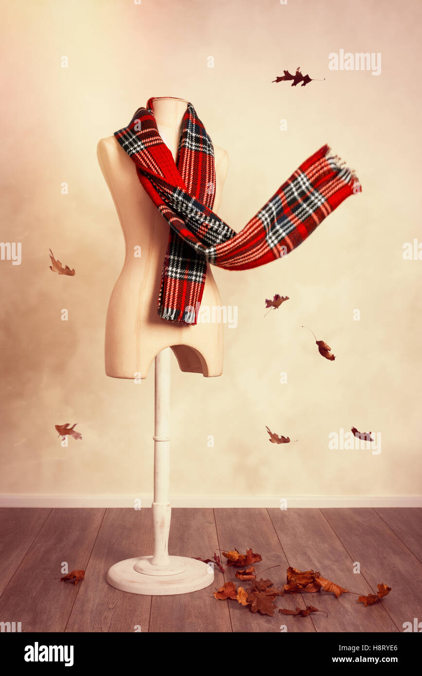 Winter wool tartan scarf with falling leaves - Stock Image