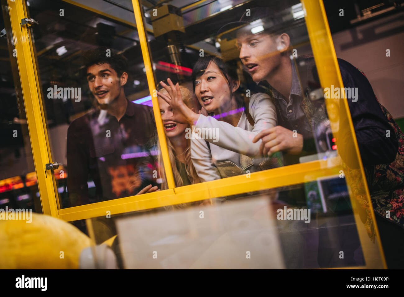 Young friends playing toy grabbing game at game room. Four young people playing at toy vending machine. - Stock Image