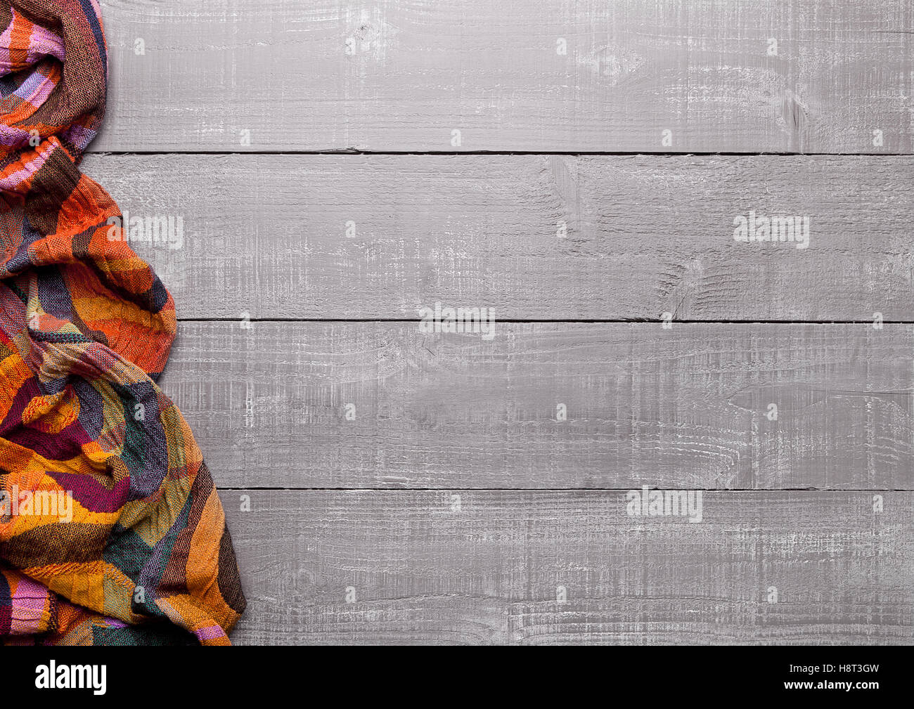 Warm soft wool scarf on wooden background texture - Stock Image
