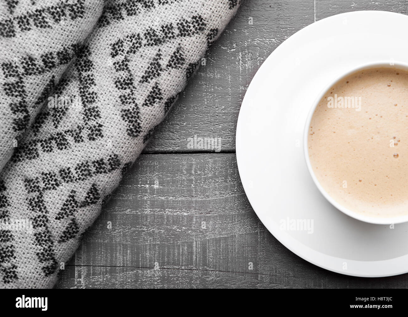 Cup of cappuccino with grey wool scarf on wooden background - Stock Image
