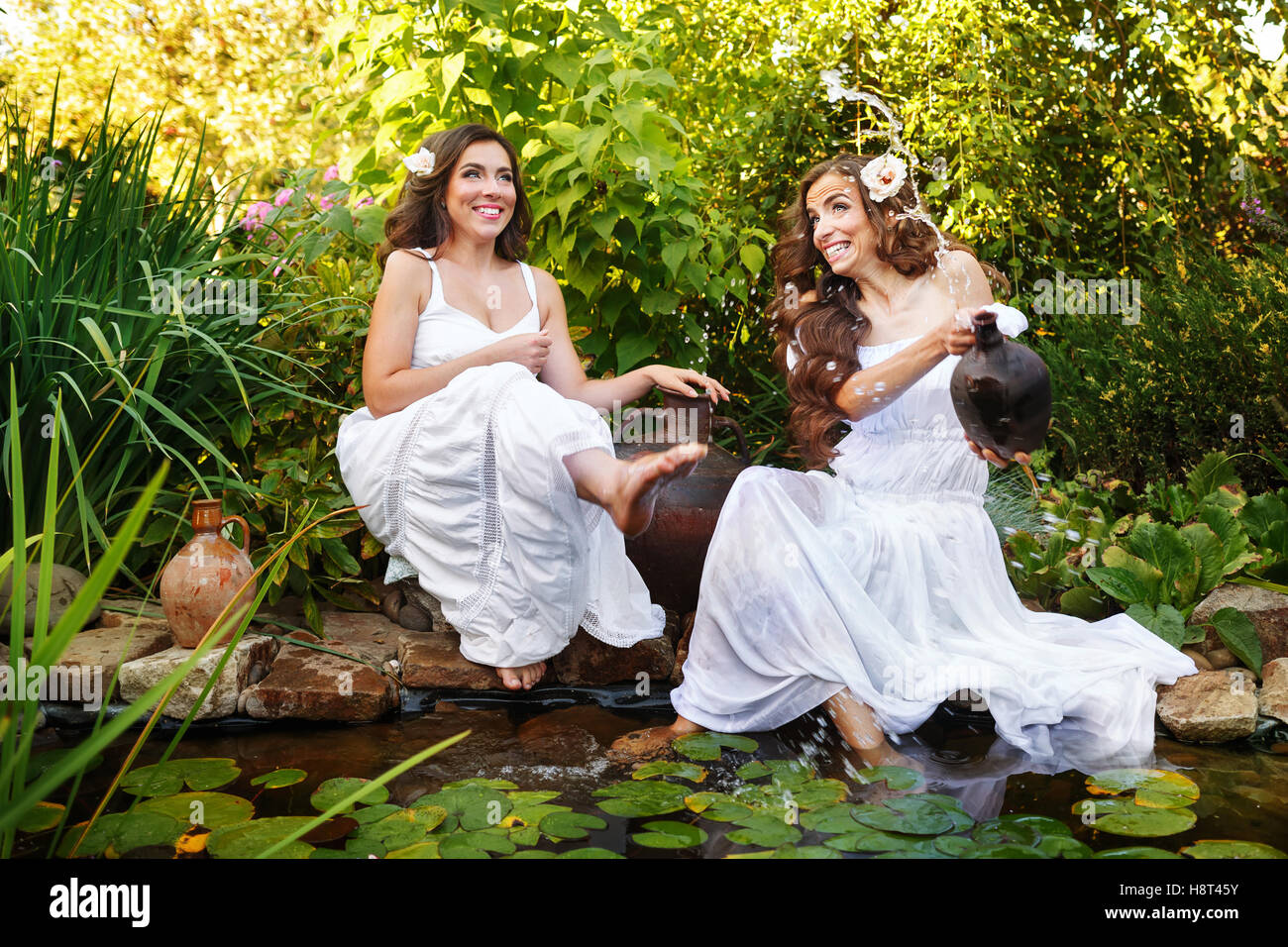 Two Cute Sisters In White Dresses At The Pond With Water Lilies