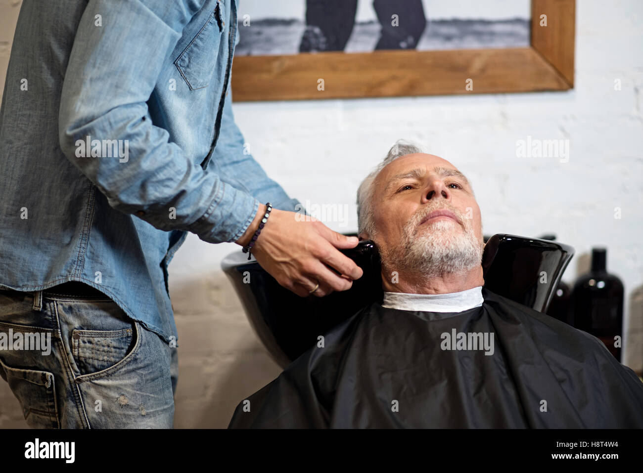 Nice old man waiting for washing hair in barbershop Stock Photo