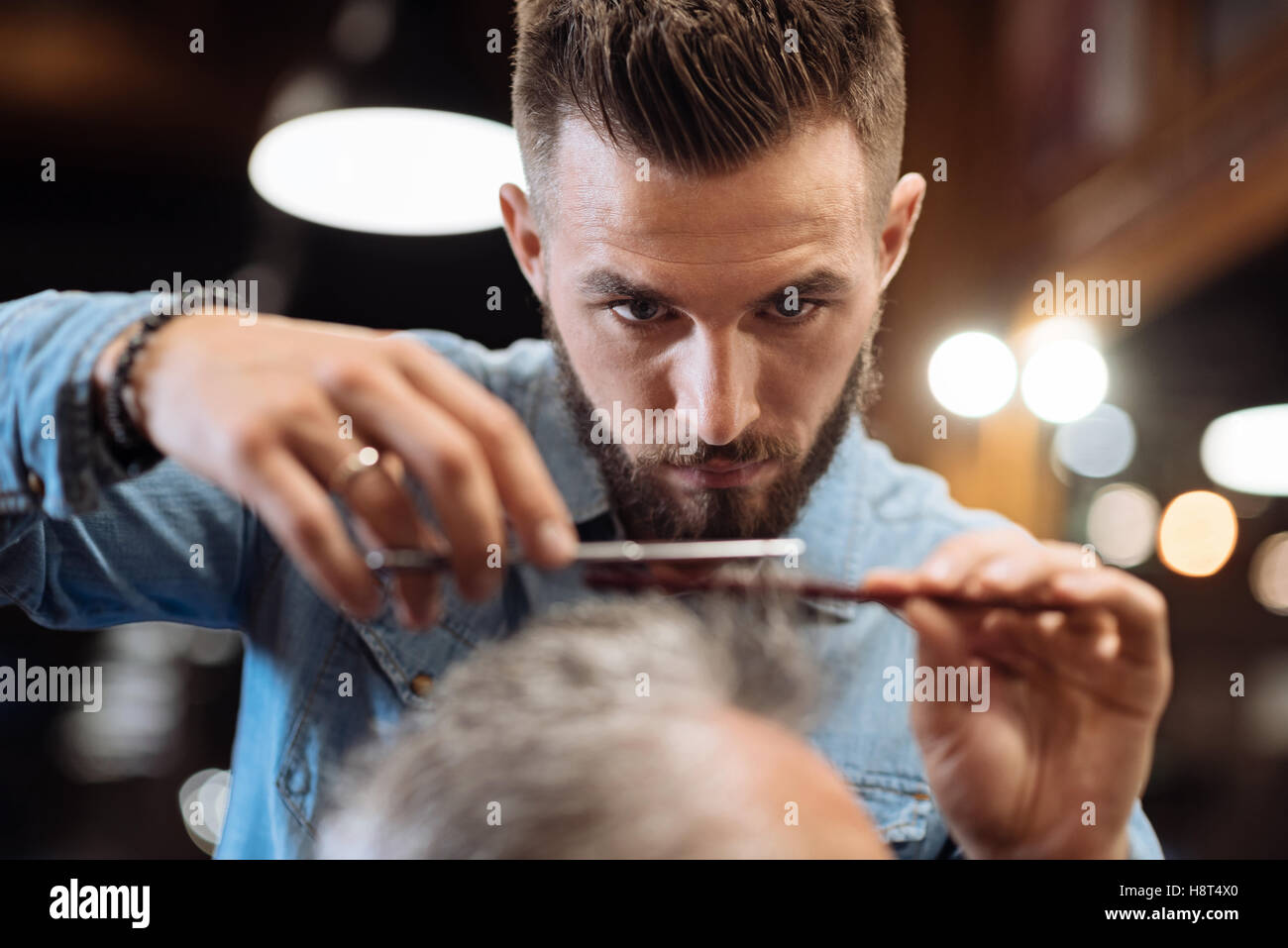 Close up of young male hairdresser cutting hair - Stock Image