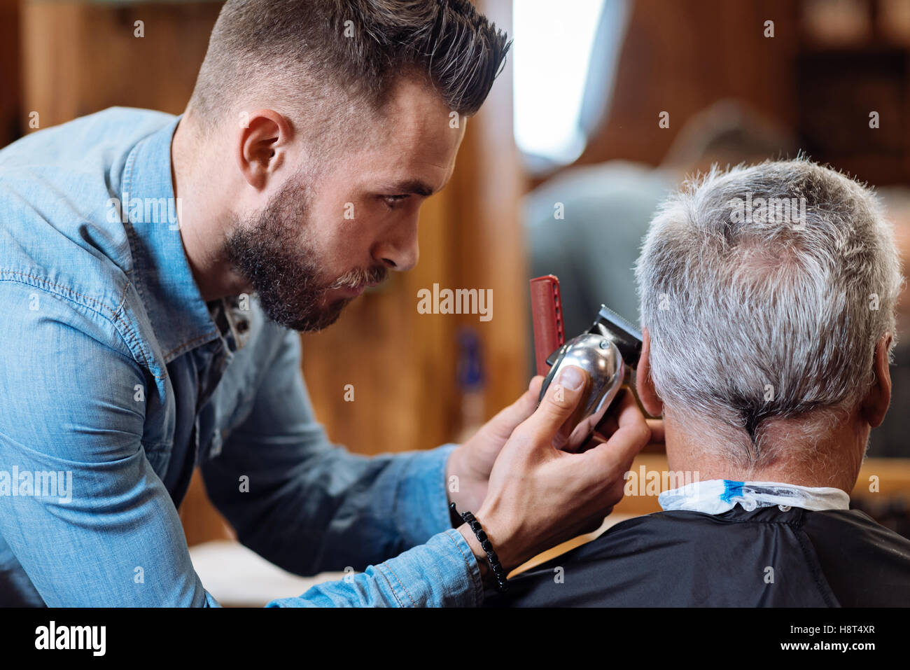 Close up of hairstylist trimming senior client hair - Stock Image