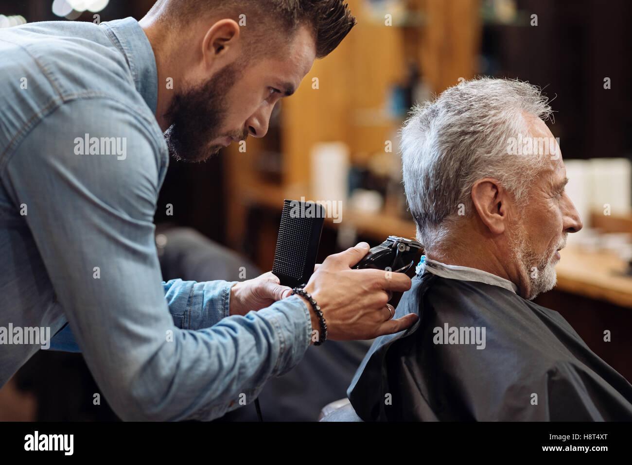 Hairdresser trimming neck of senior client - Stock Image