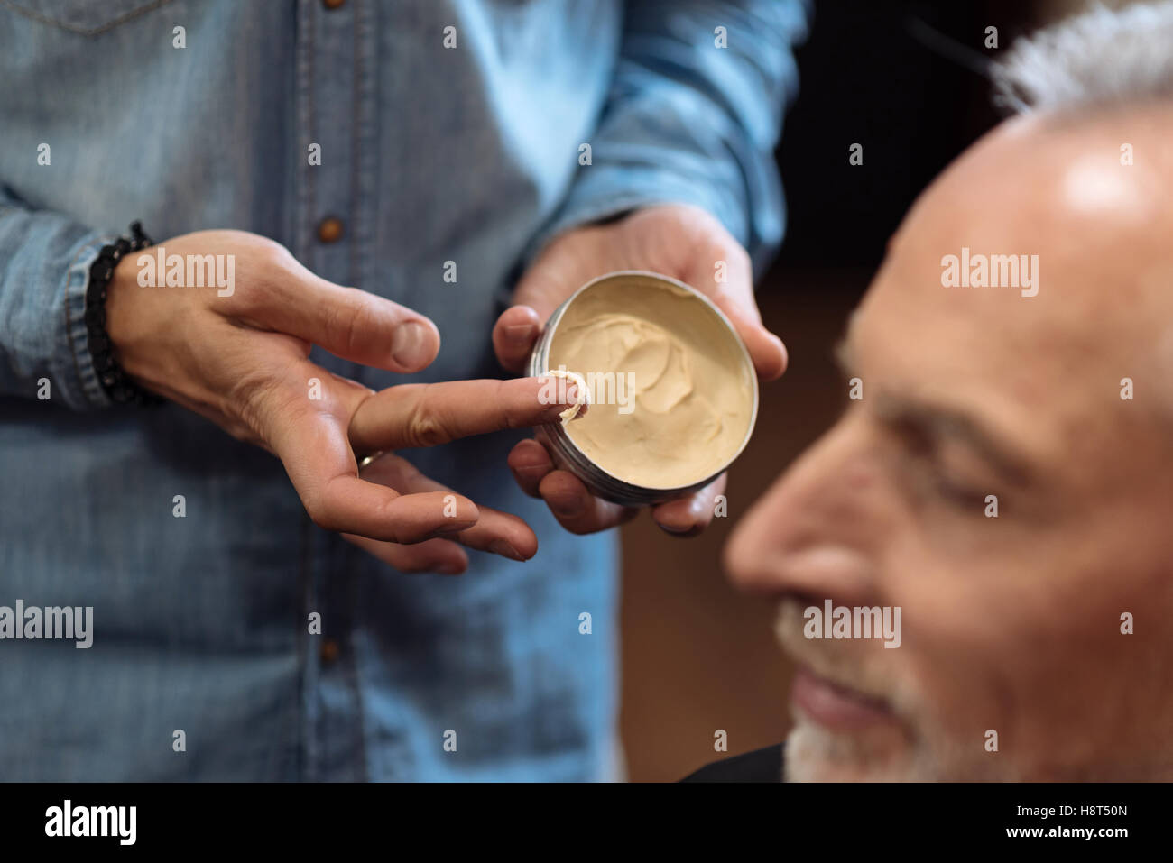 Close up of hairstylist holding hair gel - Stock Image