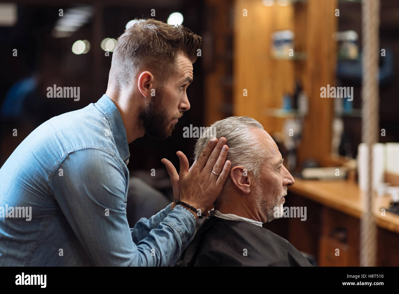 Handsome barber styling hair of senior man - Stock Image