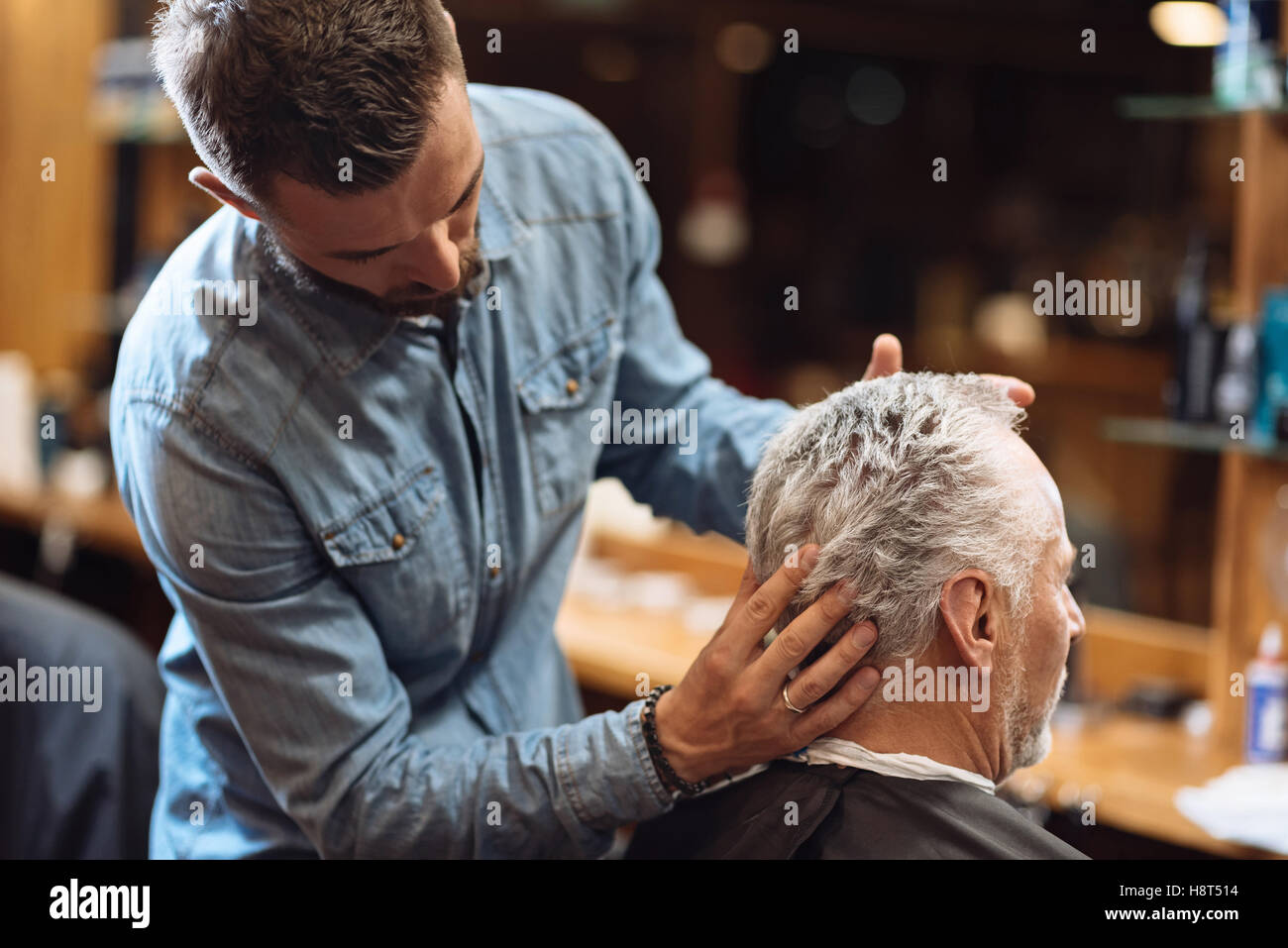 Back view of barber styling seniors client hair - Stock Image