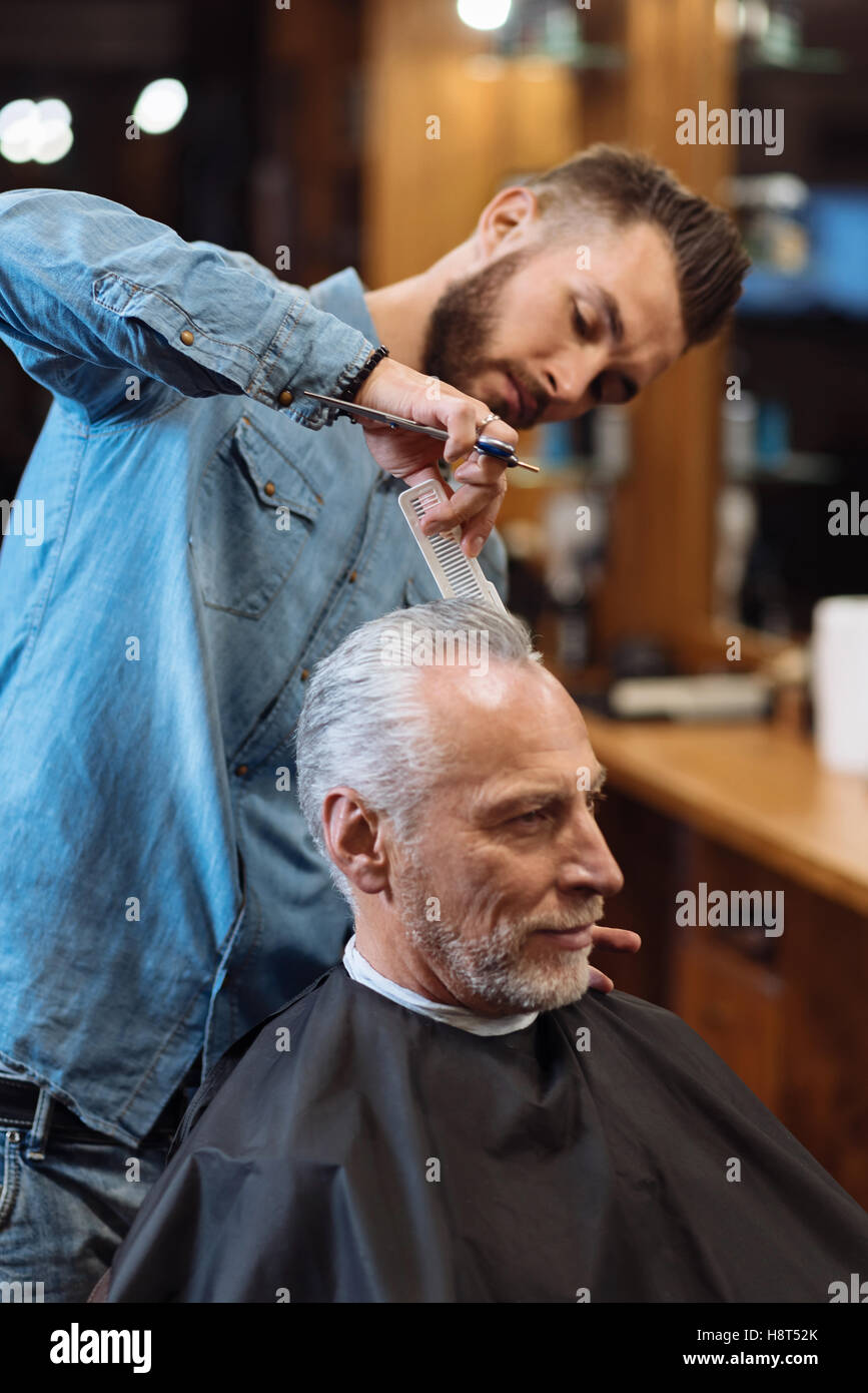 Handsome hairdresser making haircut to senior man - Stock Image