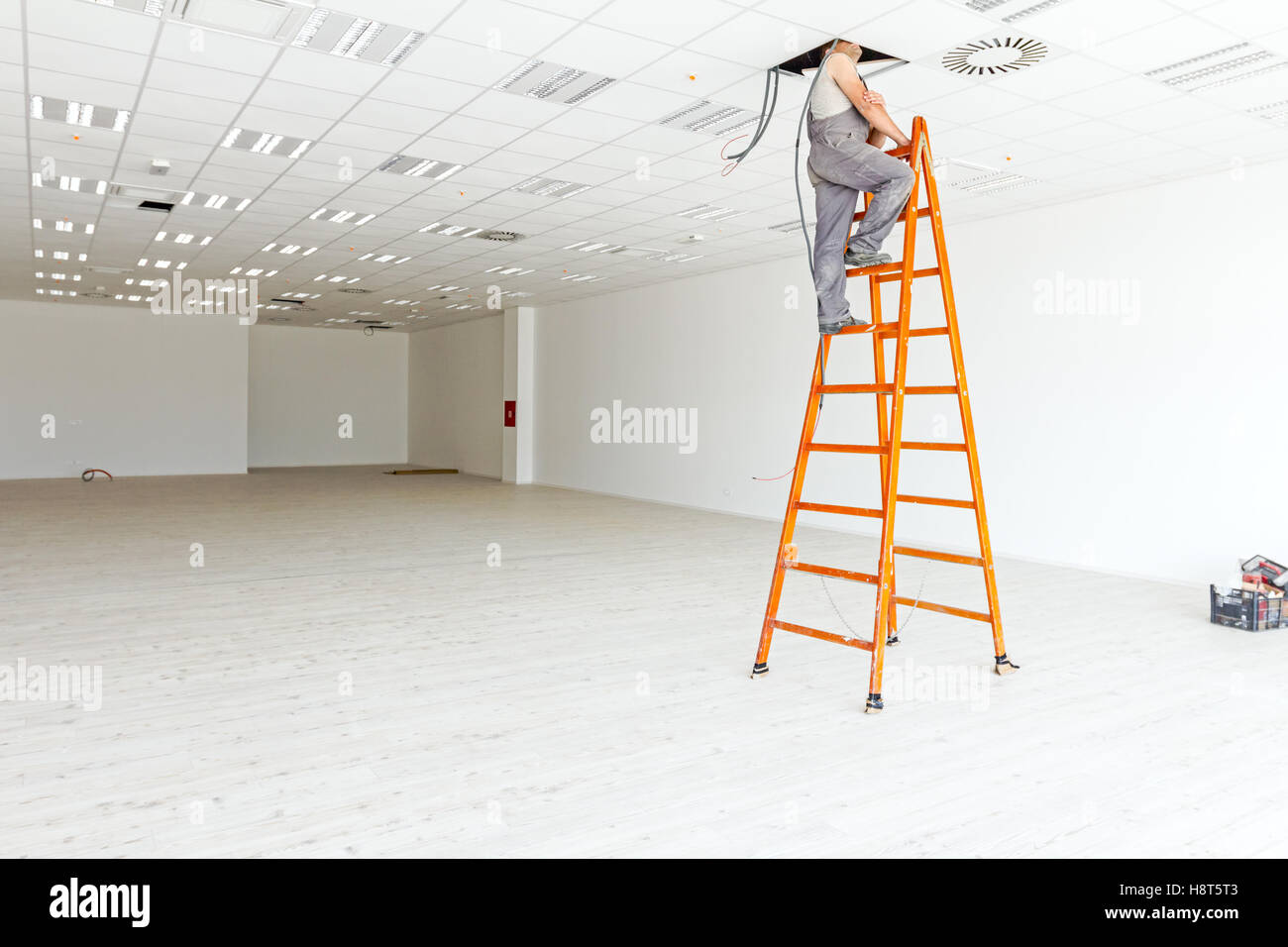 Electrician is on stepladder peering through a hole in the ceiling of a large white and empty showroom with hardwood Stock Photo