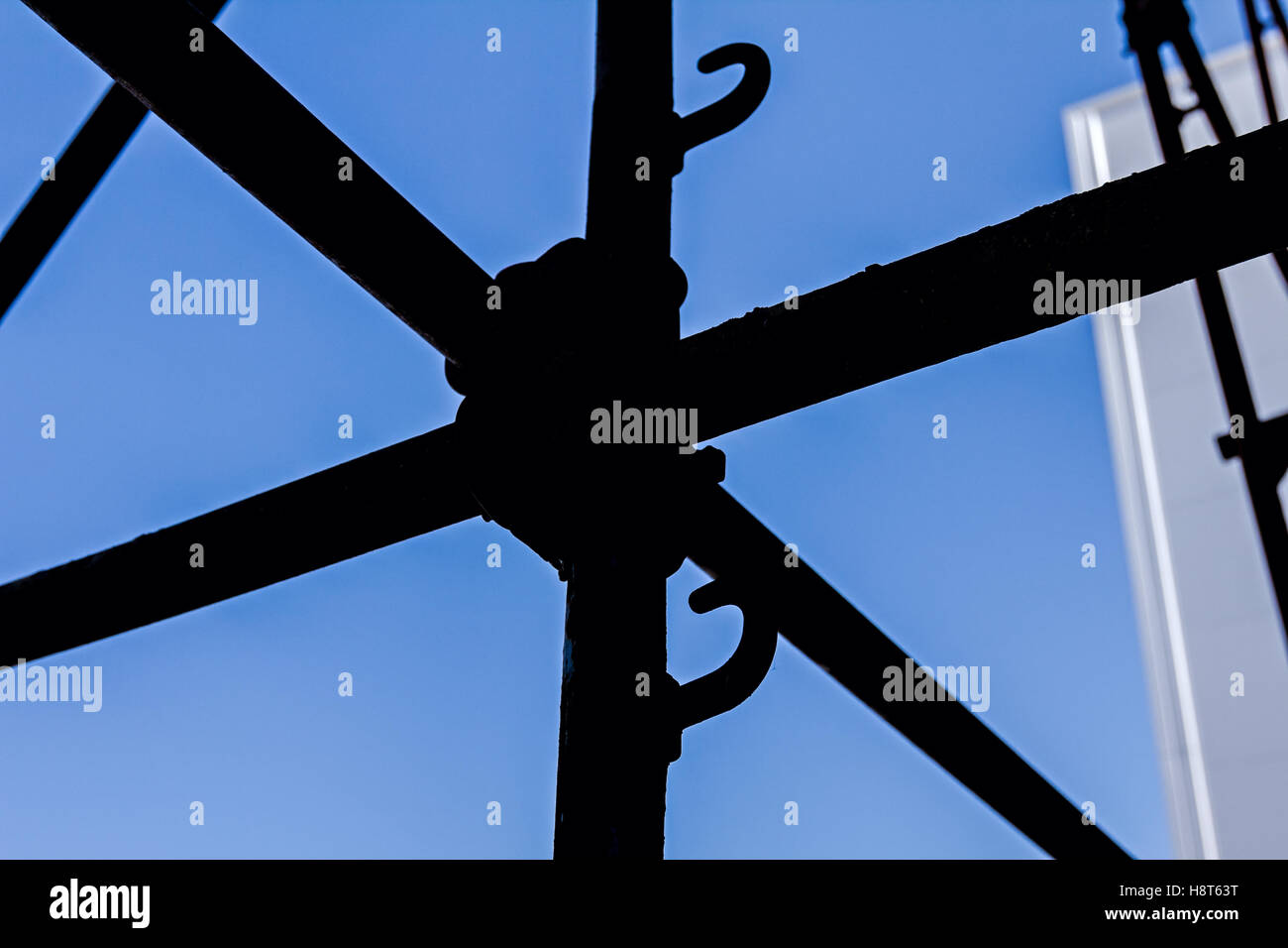 Silhouetted industrial shot node of scaffold against blue sky. - Stock Image