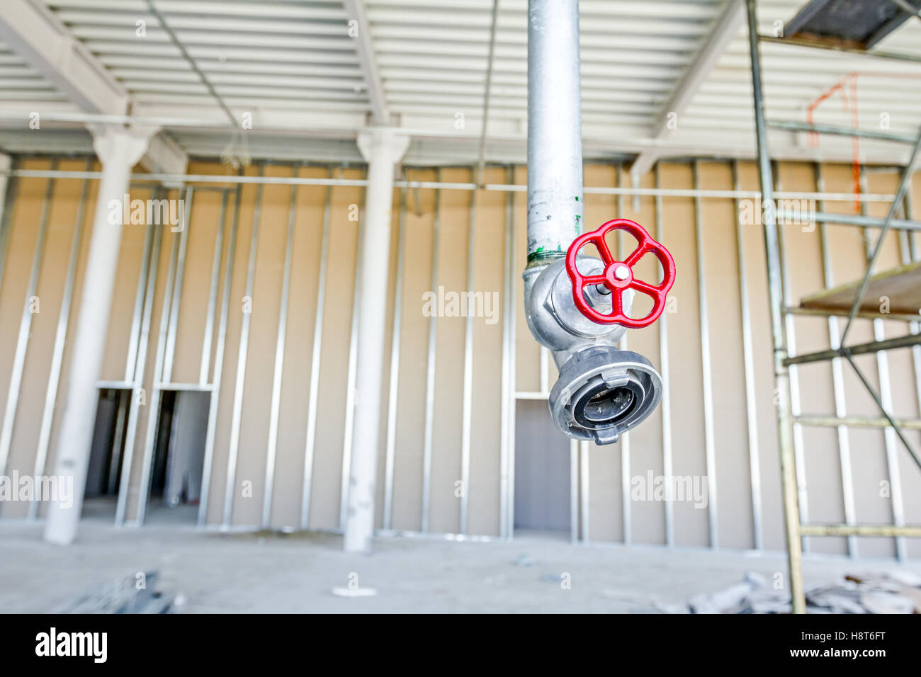 Red faucet from firefighter galvanized steel pipeline is hanging from ceiling. - Stock Image