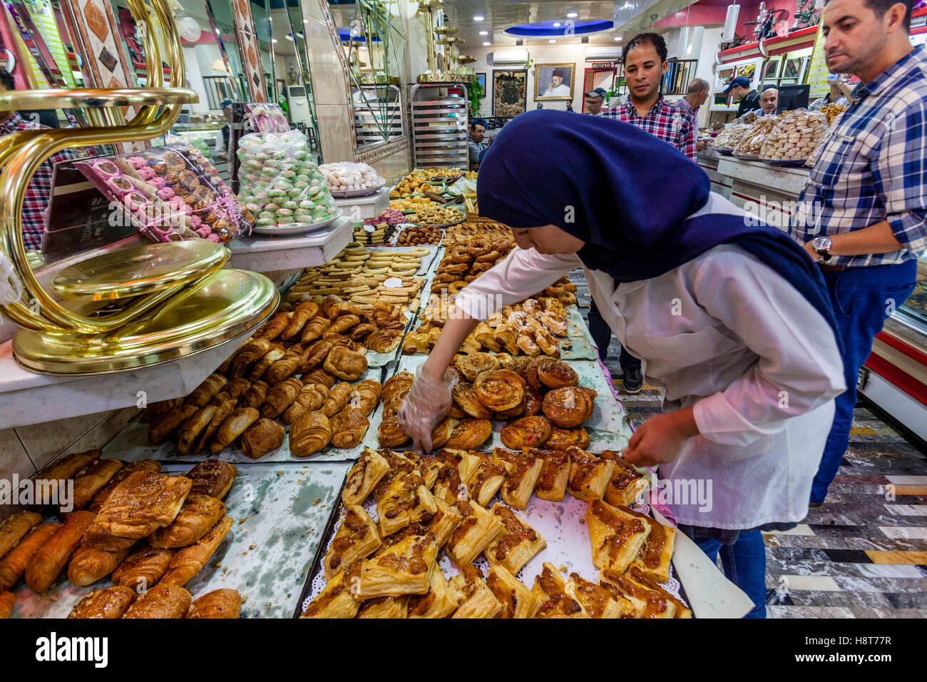 A Female Worker Selects Pastries From The Display At The Dallas Patisserie, Tetouan, Morocco - Stock Image