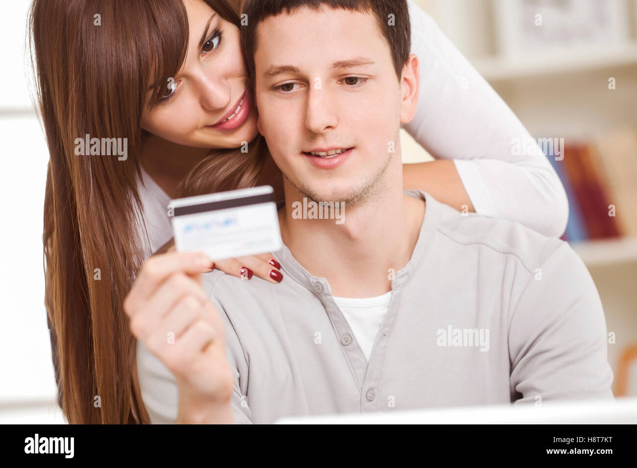 Portrait of a happy couple using laptop for banking transactions. - Stock Image