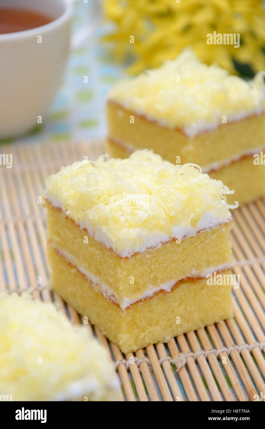 cake two layer with cheese as a toping, with a cup of hot tea as a background - Stock Image