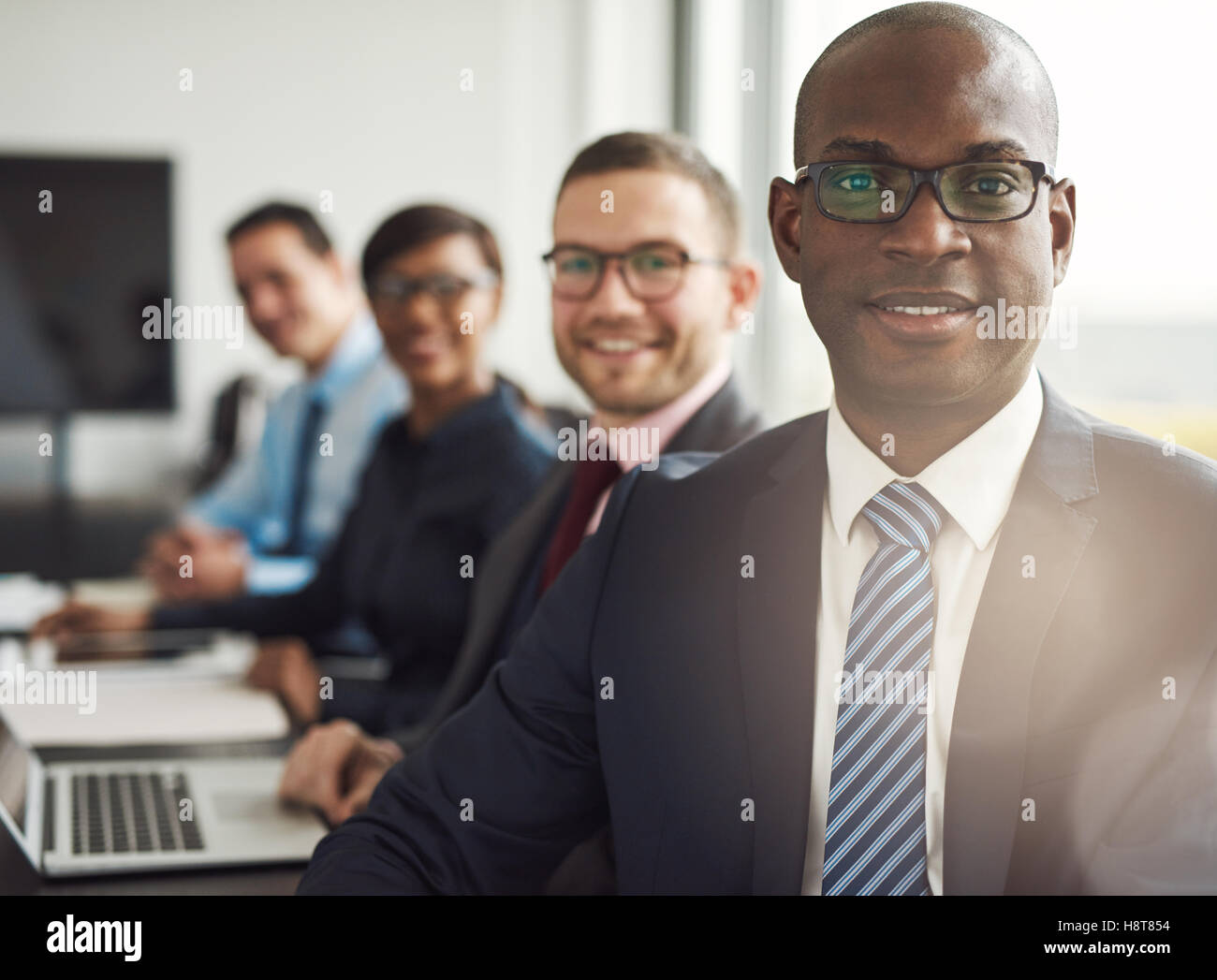 Friendly confident African businessman in a management meeting with a group of multiracial colleagues smiling at - Stock Image