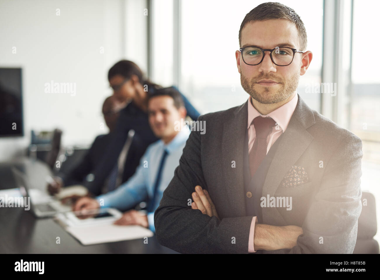 Handsome bearded professional in eyeglasses and tie standing with folded arms beside three busy coworkers in front - Stock Image