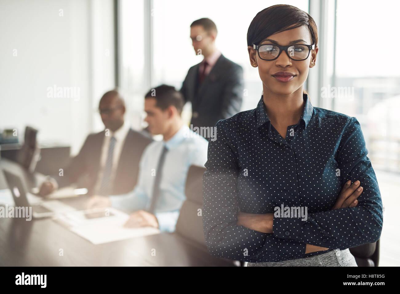 Confident young African businesswoman standing with folded arms smiling at the camera in a boardroom with male colleagues - Stock Image