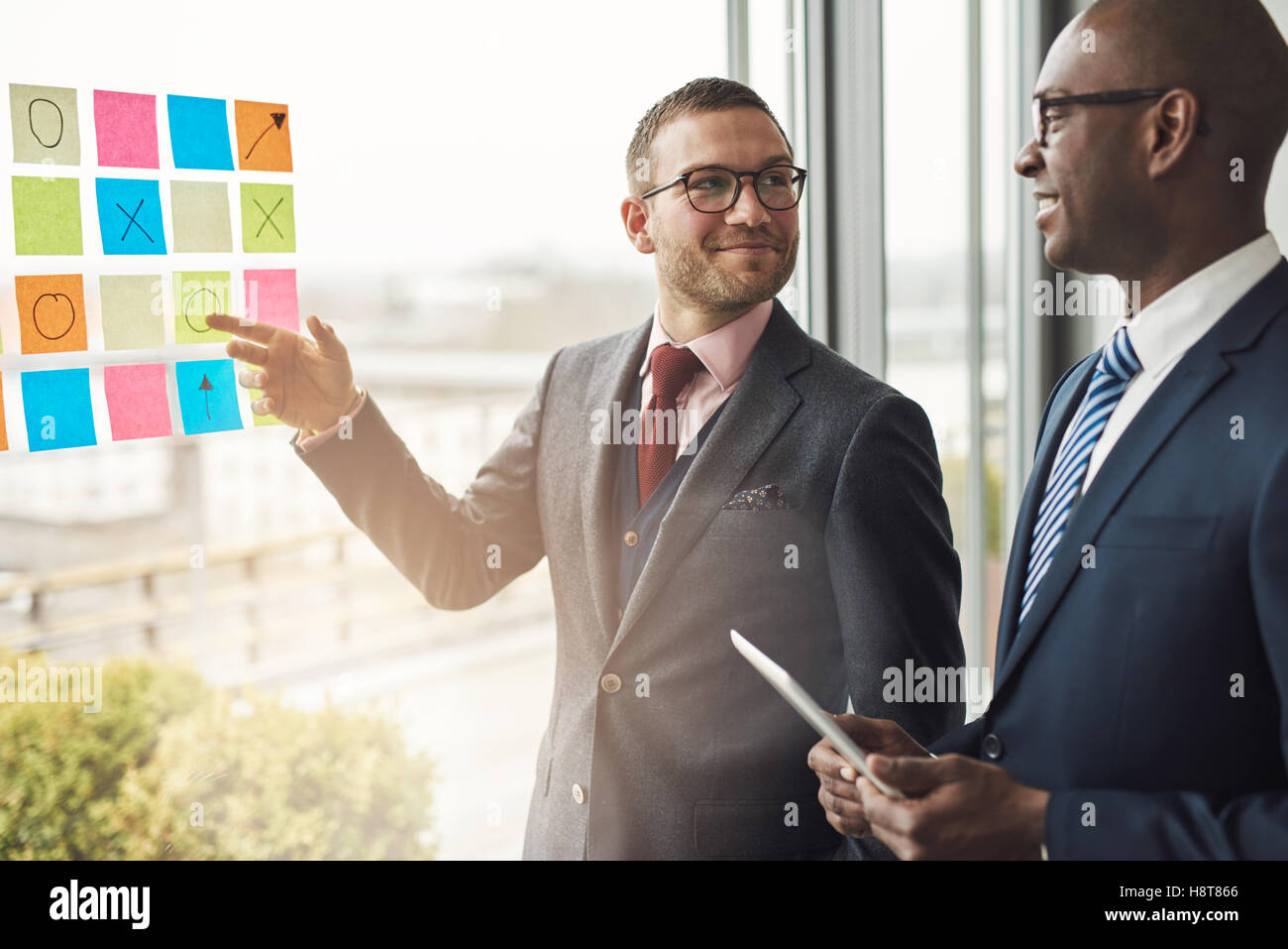 Two businessmen standing in front of a bright window with flare smiling as try to solve a problem laid out on colorful Stock Photo