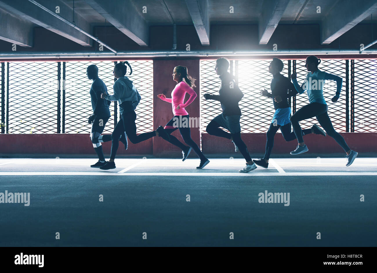 Group of diverse urban runners sprinting across the frame in an indoor car park as they workout backlit by the sun Stock Photo