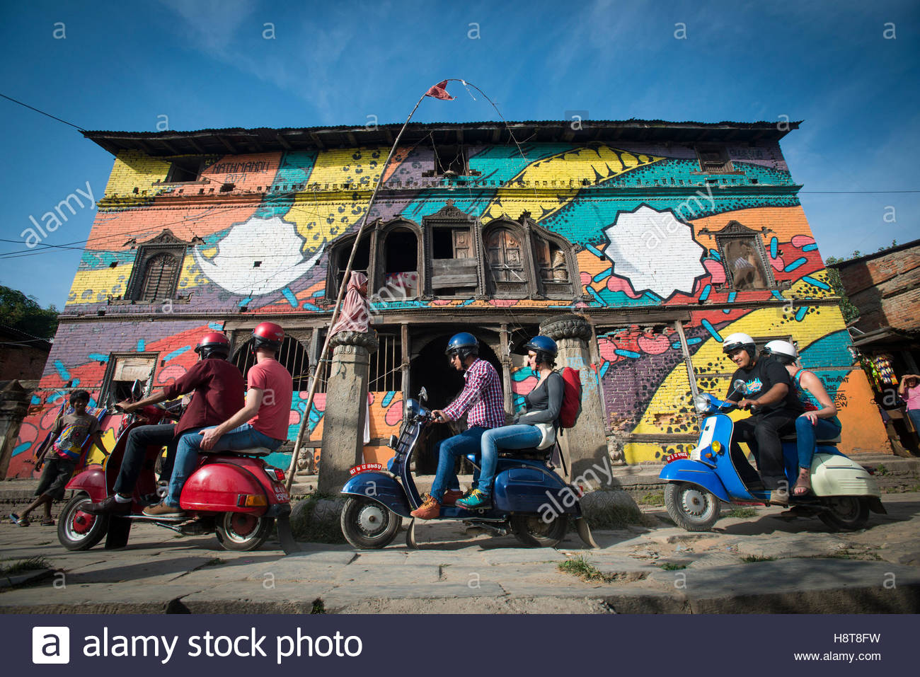 A group of tourists on scooters outside a brightly painted mural on a building in Kathmandu in Nepal - Stock Image