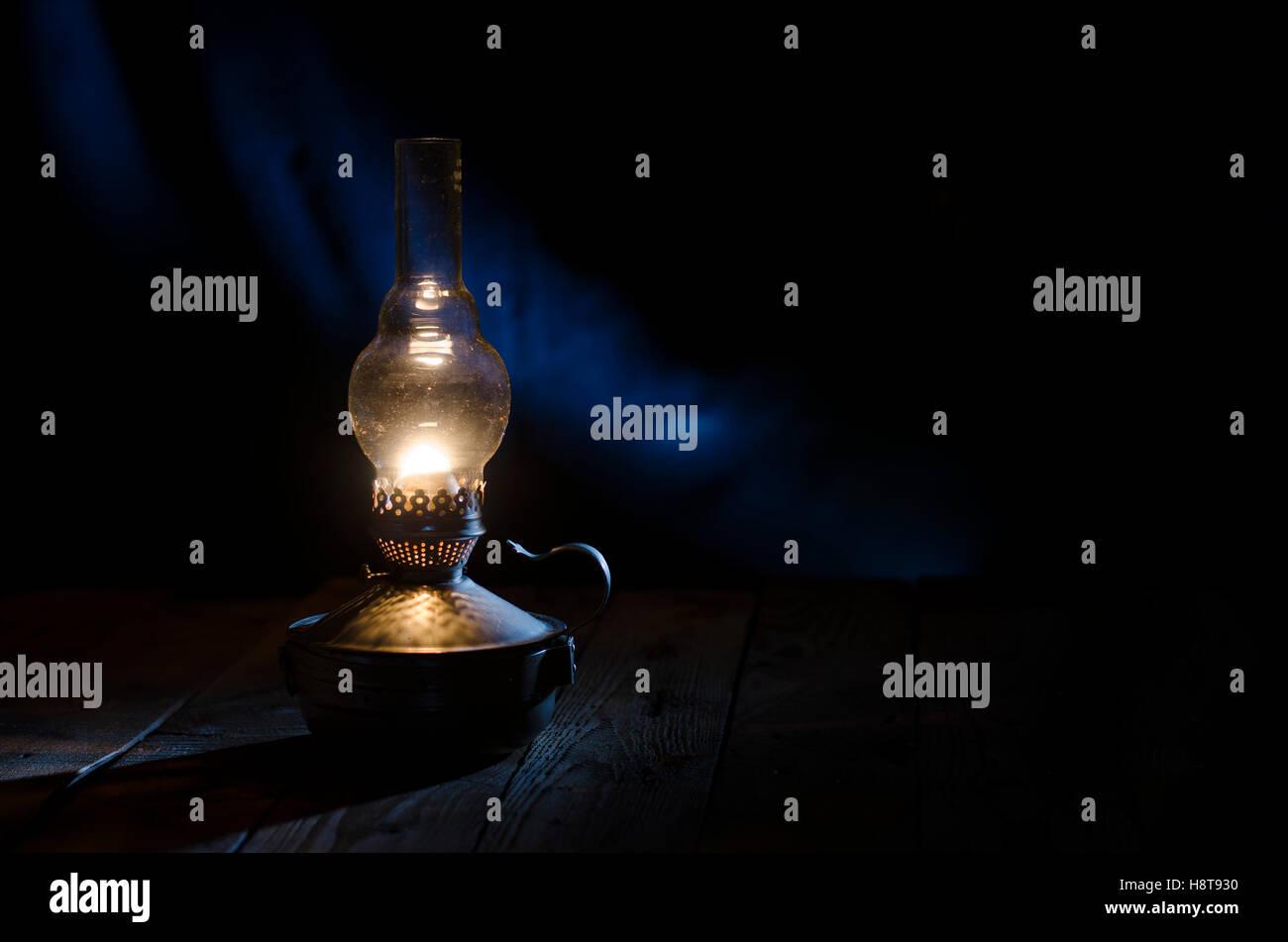 Old kerosene lamp on the rough wooden table. - Stock Image