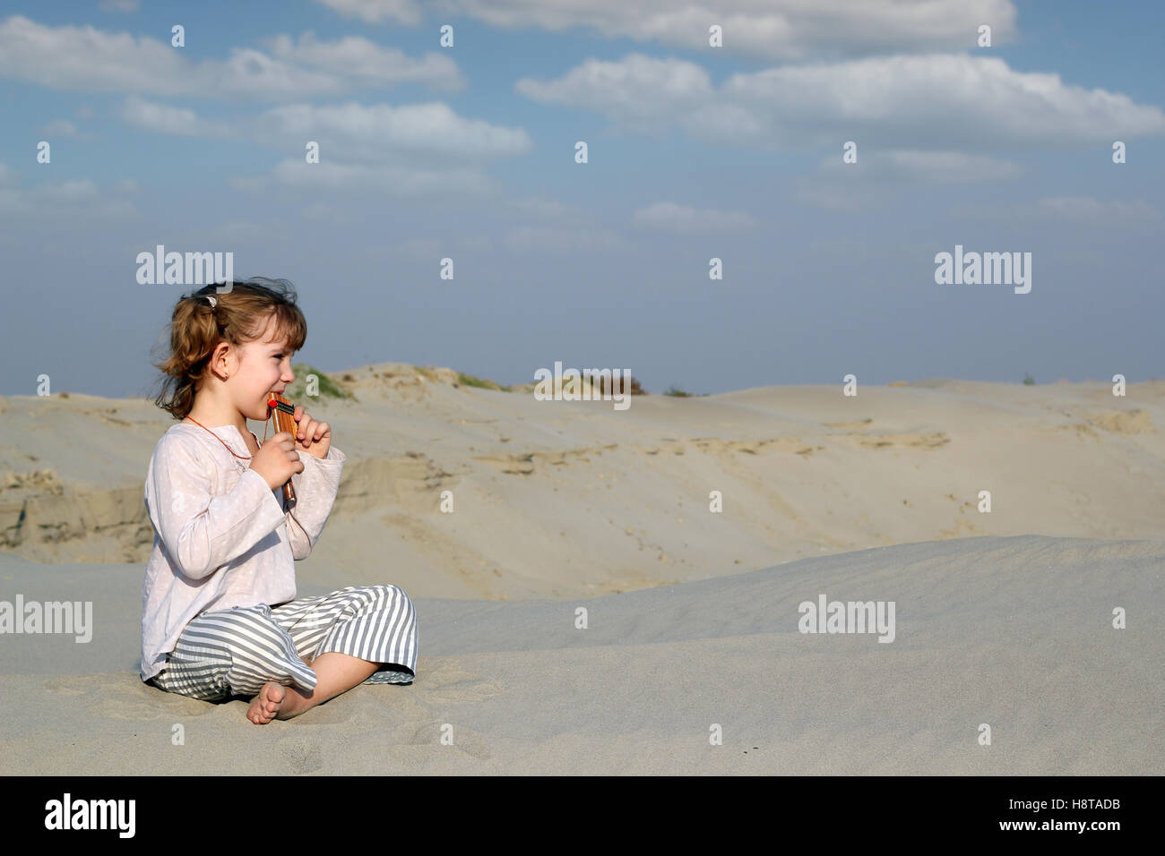 little girl sitting on sand and play music - Stock Image
