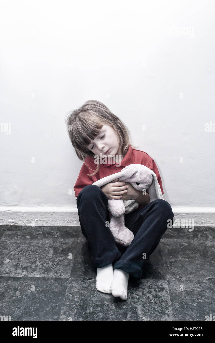 A young four year old little girl sitting on the floor with an old toy looking sad. - Stock Image