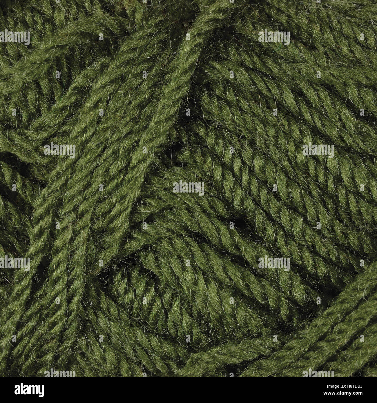 Natural green fine wool threads texture, textured clew skein macro closeup background pattern - Stock Image