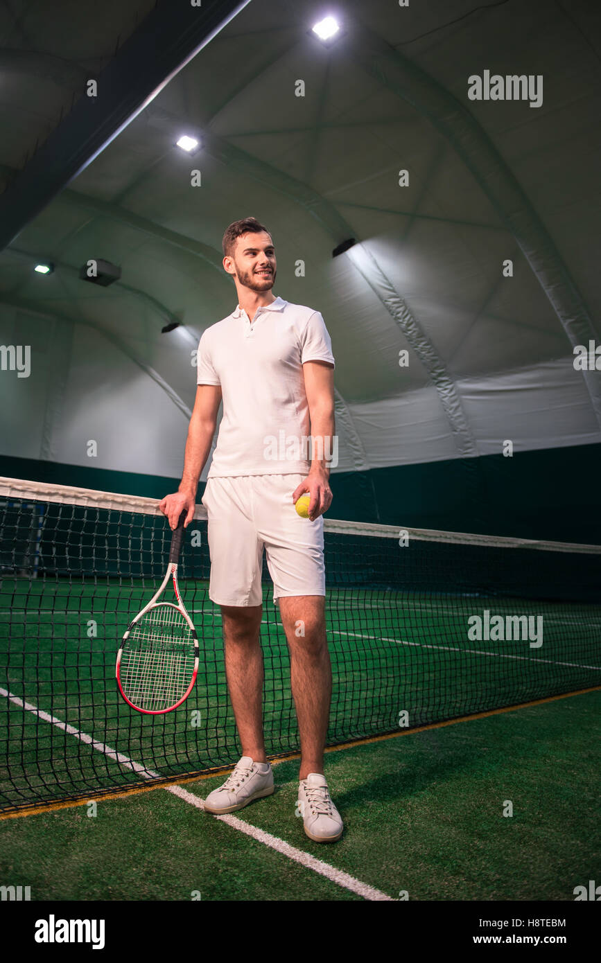 Delighted handsome tennis player going to play Stock Photo