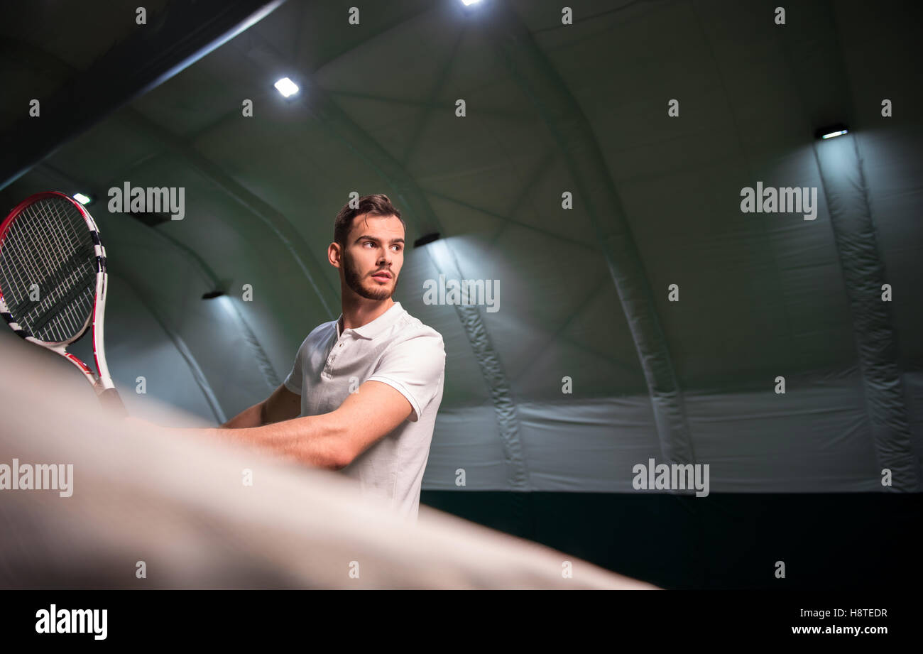 Concentrated sportsman playing tennis. Stock Photo