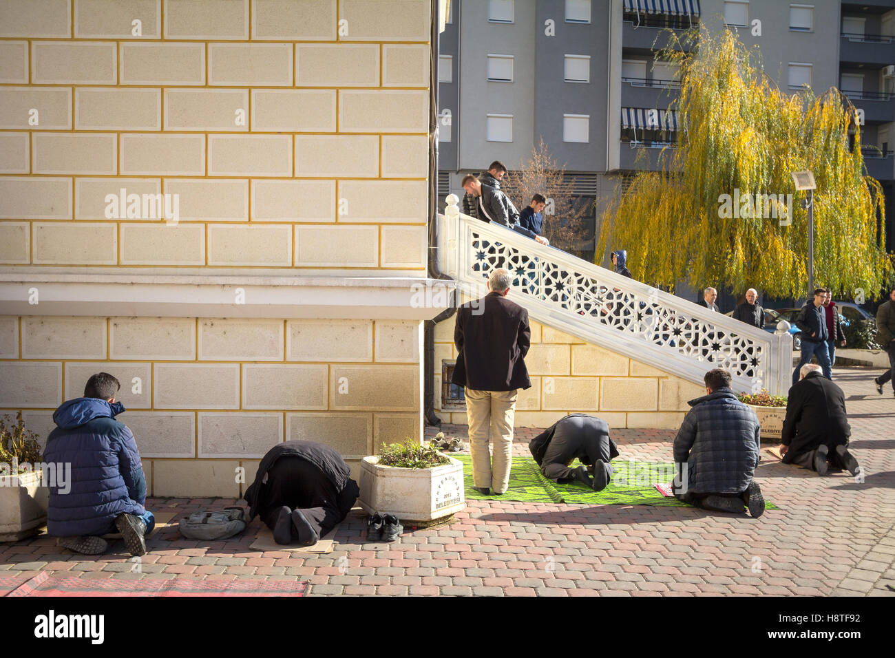 Kosovo Albanian muslims praying in front of the Isa Beg Mosque in Mitrovica, Kosovo - Stock Image