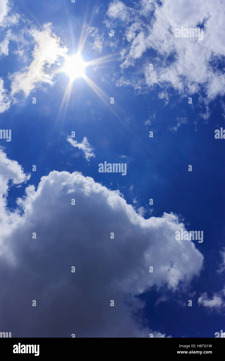The sun shines through the cracks clouds during summer season. - Stock Image