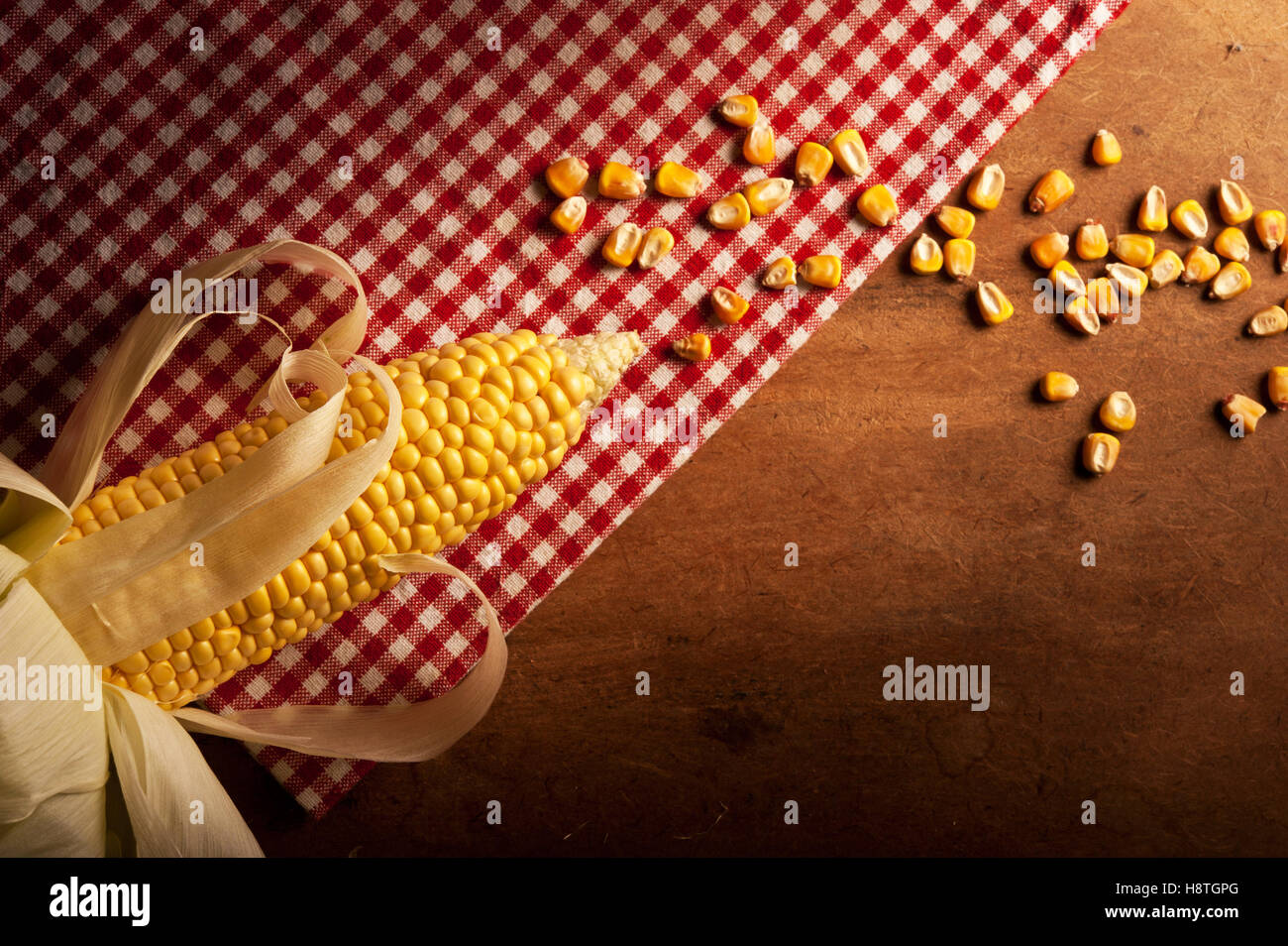 corn maize lying lying on red dish-cloth in rustic style - Stock Image