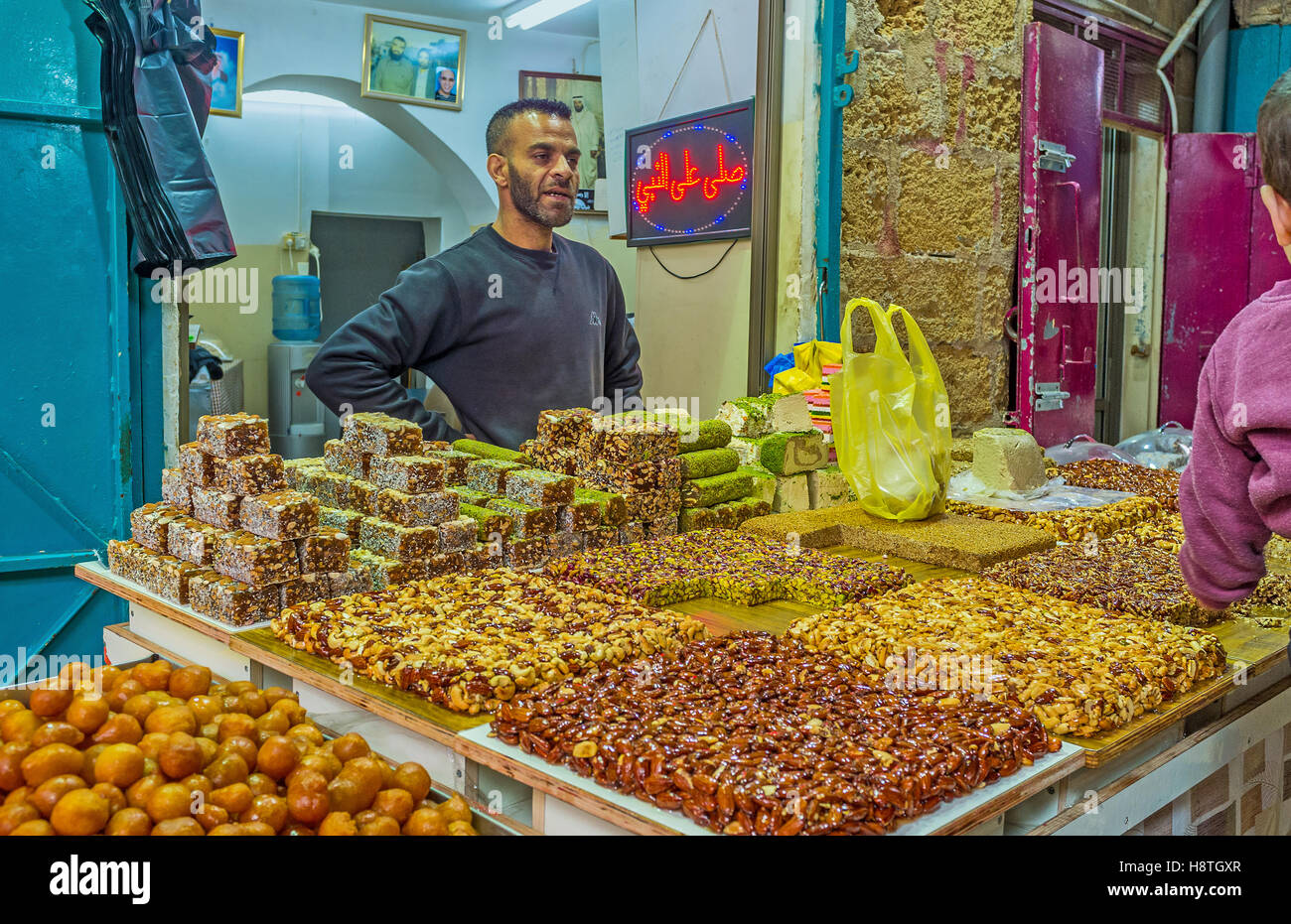 The merchant in Turkish bazaar offers the tasty nuts' gozinaki, lokum, lokum and other desserts - Stock Image