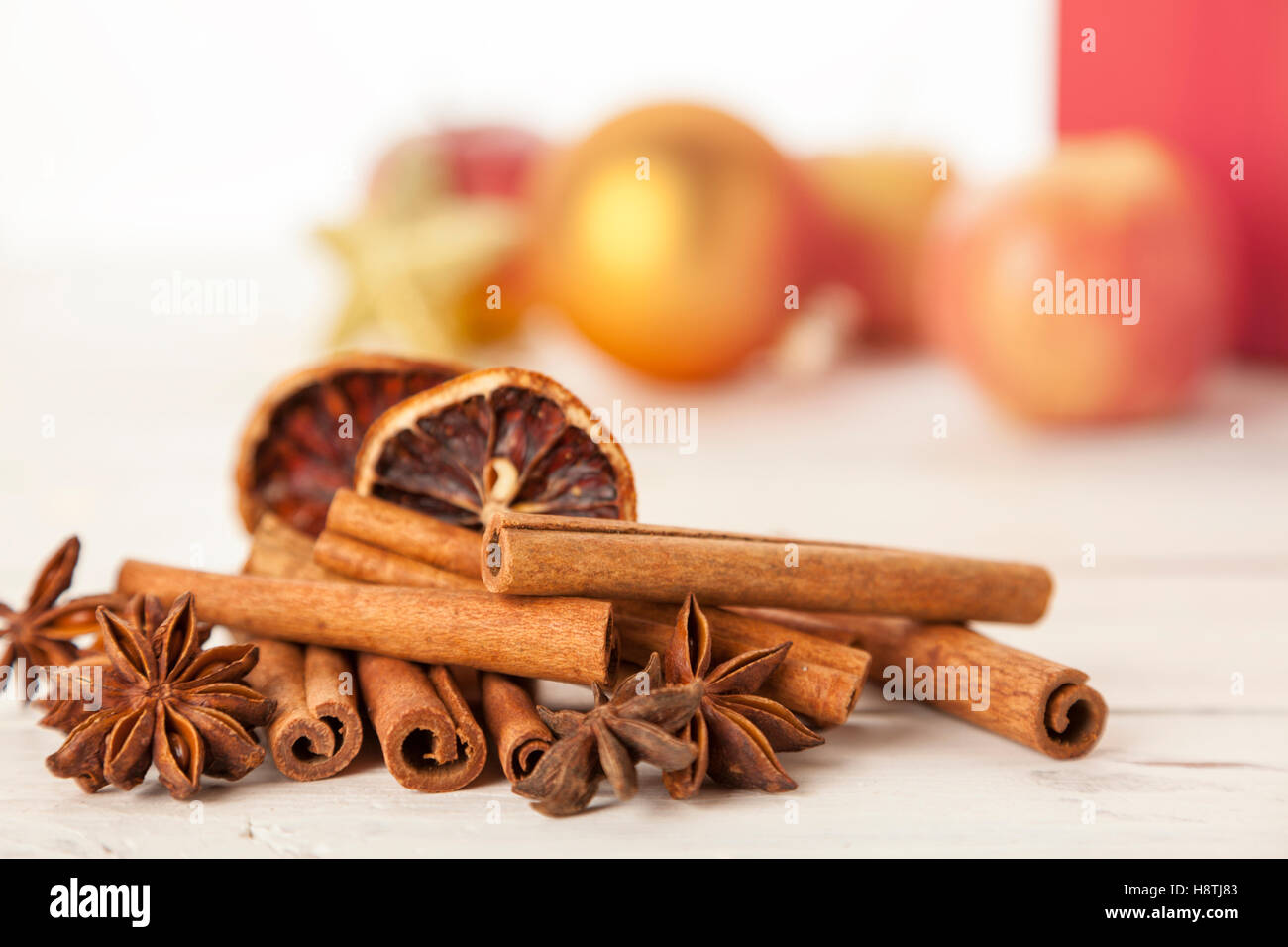 heap of cinnamon quills, star anise and dried orange slices, Christmas decoration out of focus in background - Stock Image