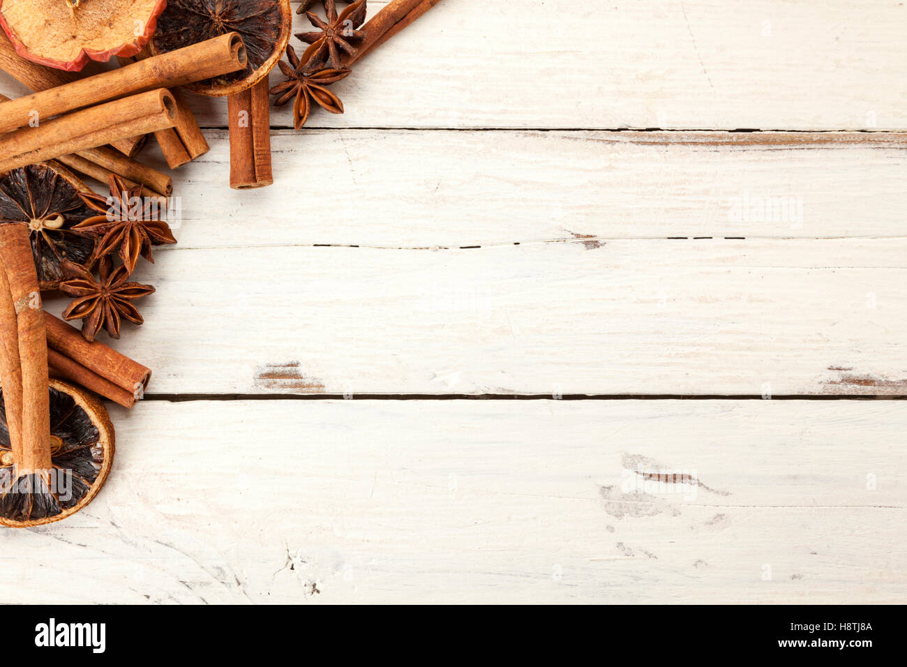 Christmas background with cinnamon sticks, anise and dried fruit on white painted wood Stock Photo