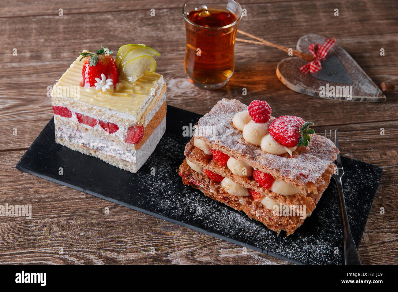 cream cake strawberry frosting mille feuille dessert sweet on black stone Stock Photo