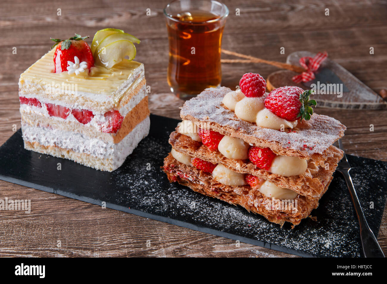 cream cake strawberry frosting mille feuille dessert sweet on black stone - Stock Image