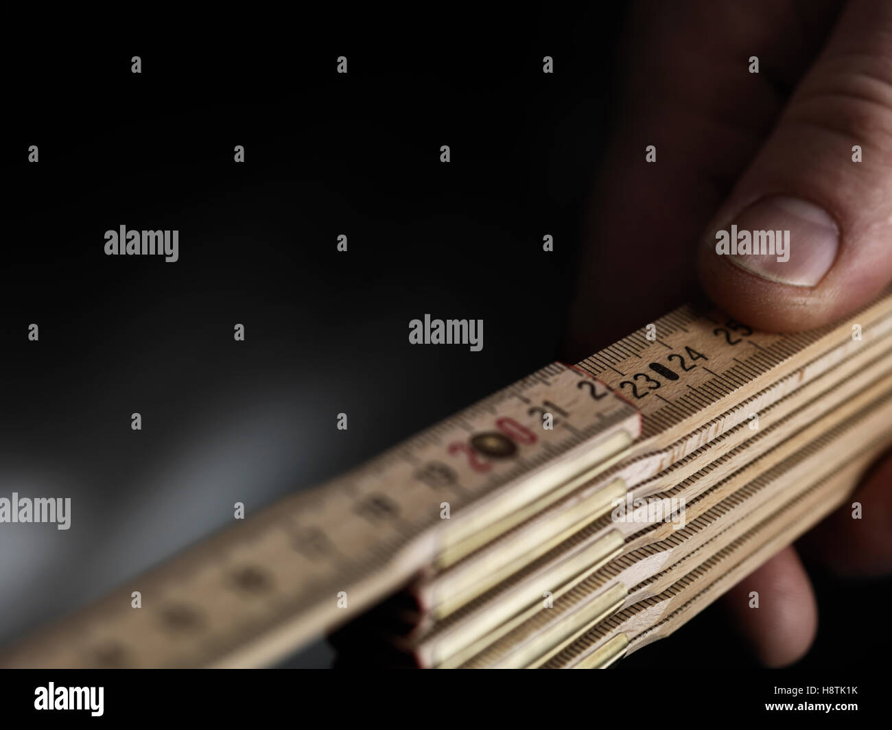 Close up wooden folding ruler with a hand - Stock Image