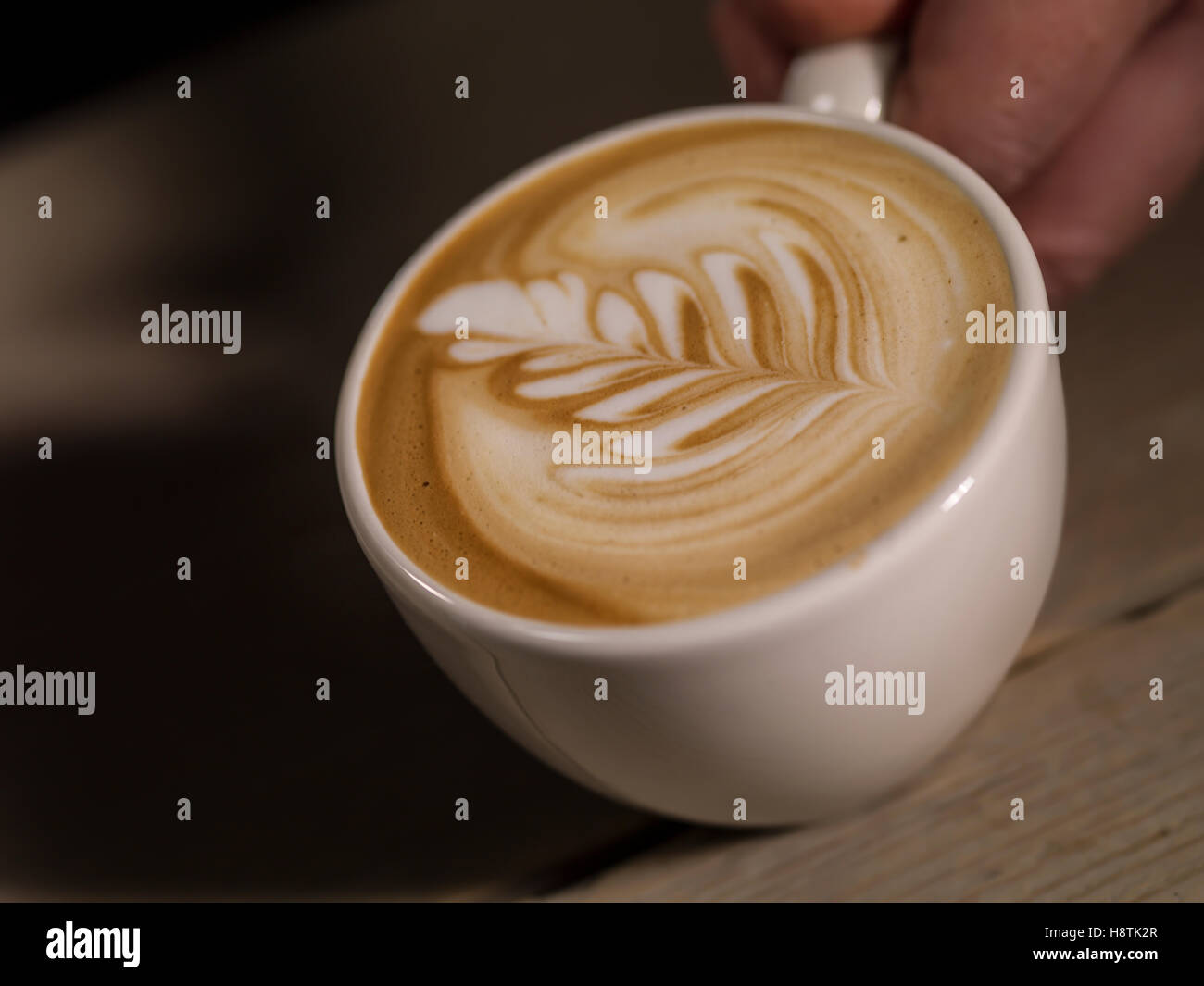 Making latte Art on a Cappucinno on a dark wooden background - Stock Image