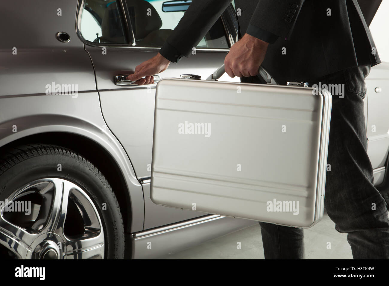 Hand on handle. Close-up of man in formalwear opening a car door with a briefcase - Stock Image